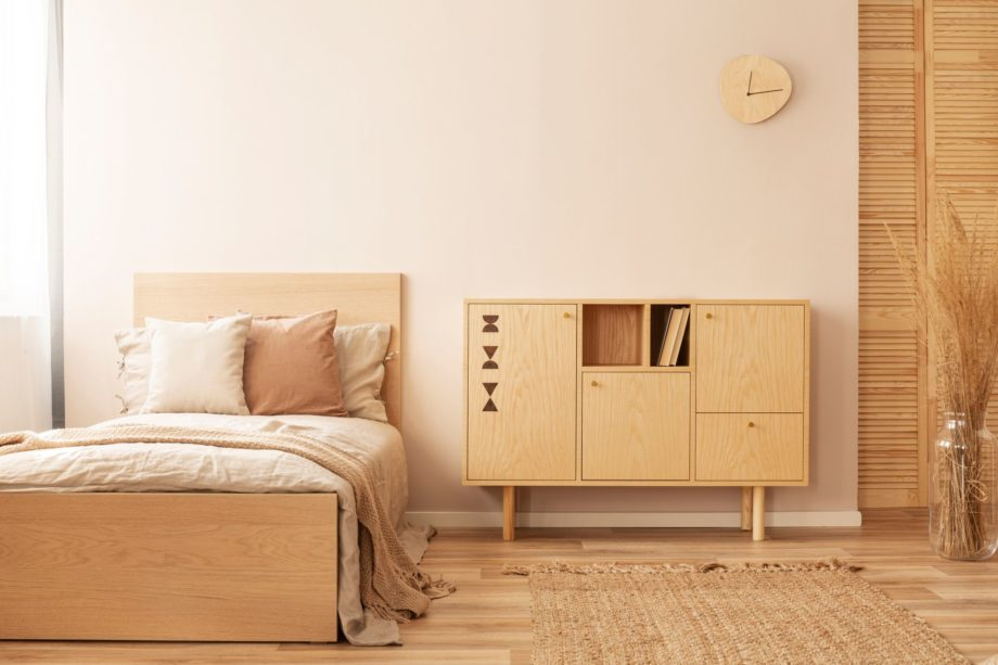 Single,Wooden,Bed,With,Beige,Bedding,And,Blanket,Next,To