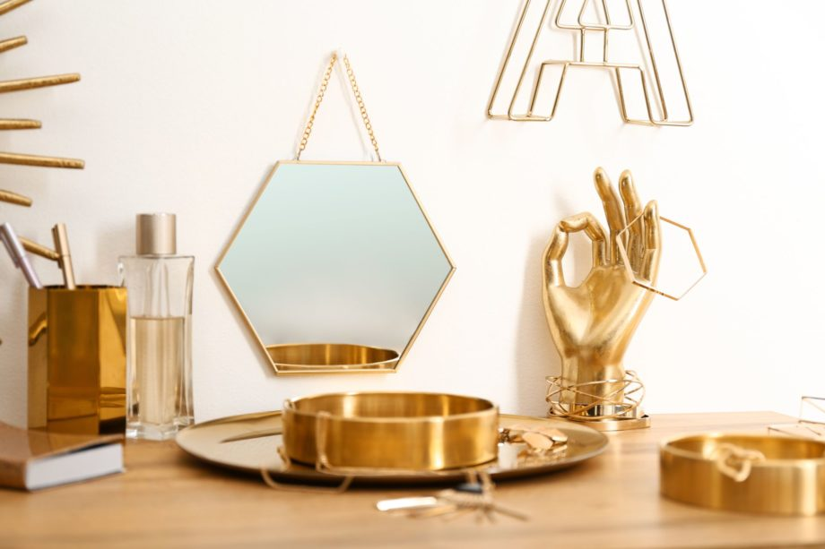 Composition,With,Gold,Accessories,On,Dressing,Table,Near,White,Wall