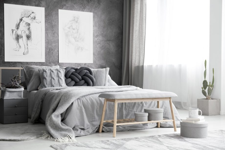 Wooden,Bench,And,Boxes,In,Monochromatic,Bedroom,Interior,With,Drawings